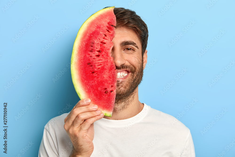 Fototapety, obrazy: Taste of summer concept. Cheerful young man covers half of face with big slice of watermelon, has oraganic healthy nutrition, dressed casually, poses on blue background, enriches with vitamins.