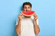 canvas print picture - Funny man holds half of red watermelon near face, has glad surprised look, dressed casually, has healthy summer nutrition. European guy poses with tasty tropical fruit against blue background