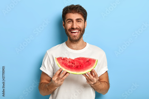 Waist up shot of smiling man enjoys summer day, holds slice of fresh ripe watermelon, wants to eat delicious fruit, wears casual white t shirt, isolated on blue background, has picnic during weekend