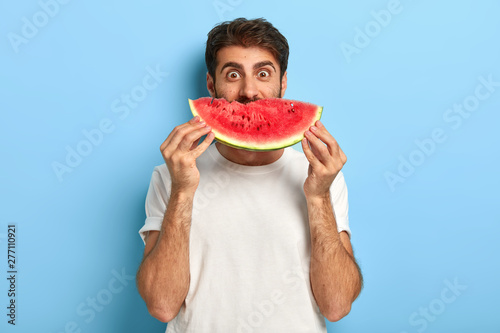 Funny man holds half of red watermelon near face, has glad surprised look, dressed casually, has healthy summer nutrition. European guy poses with tasty tropical fruit against blue background - 277110921