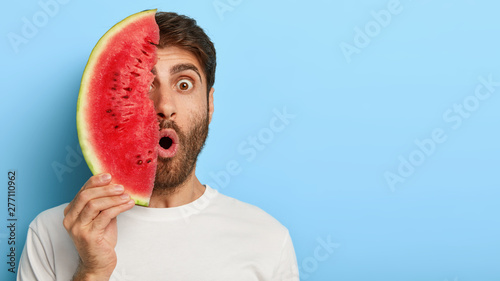 Keuken foto achterwand Kruidenierswinkel Stupefied man enjoys eating tropical fruit, covers half of face with slice of fresh watermelon, has summer holiday, eats seasonal food with vitamins, has shocked look, copy space area on right