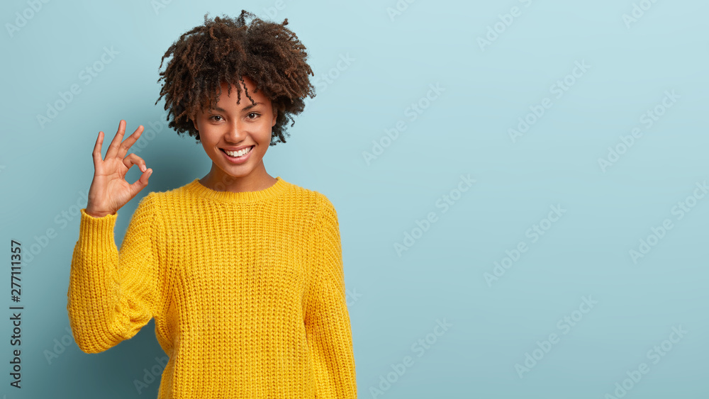 Fototapeta Okay, its fine. Charming good looking young Afro woman says no problem, shows excellent gesture, has tender smile, gives recommendation, demonstrates positive approval, dressed in yellow sweater