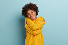 Lovely Happy African American Woman Daydreams, Embraces Herself, Recalls Romantic Date, Feels Comfort, Keeps Hands Across Body Sensually, Has Broad Smile, Wears Yellow Sweater, Poses Indoor.