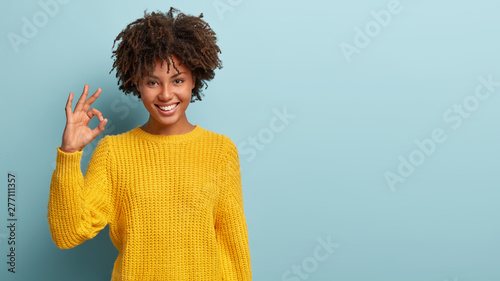 Okay, its fine. Charming good looking young Afro woman says no problem, shows excellent gesture, has tender smile, gives recommendation, demonstrates positive approval, dressed in yellow sweater - 277111357
