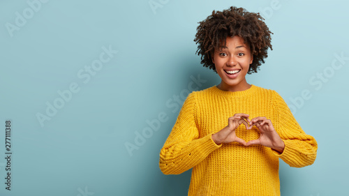Tablou Canvas Pleasant looking smiling woman with Afro hairstyle makes heart gesture, confesses boyfriend in hearwarming feelings, shows love sign, wears oversized yellow jumper