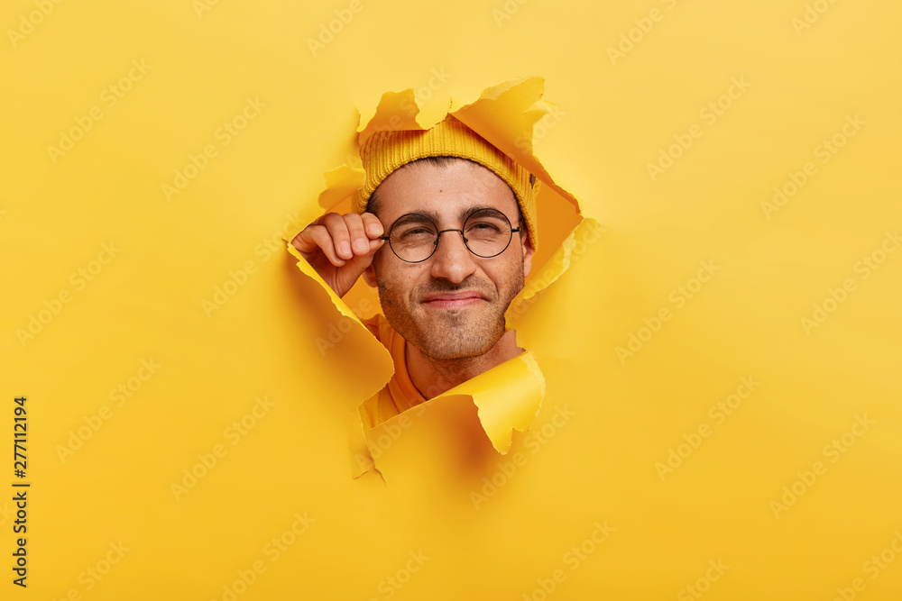 Fototapety, obrazy: Male face in paper torn hole. Man looks curiously, has happy gaze, touches frame of glasses, poses over yellow background, makes funny photos, tries to see something in distance, has bad vision