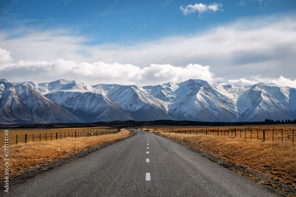 Fototapety, obrazy: A long straight road leading towards a snow capped mountain in New Zealand.
