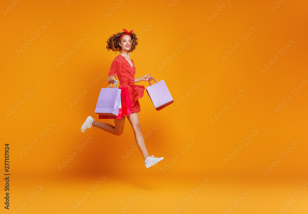 Fototapeta concept of shopping purchases and sales of happy   girl with packages  on yellow background.