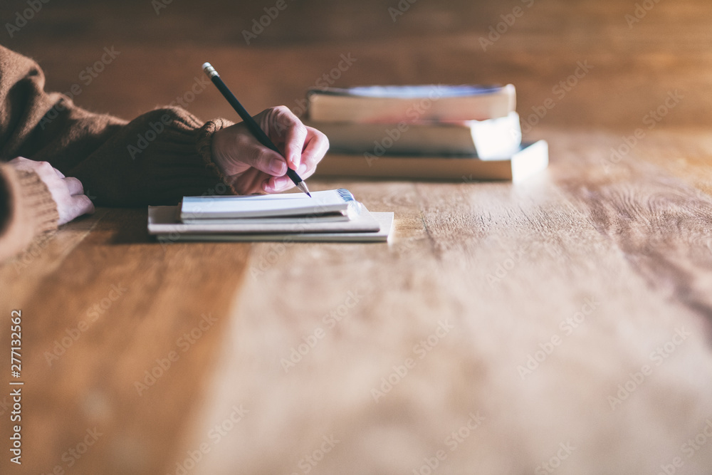 Fototapety, obrazy: Closeup image of a woman writing on blank notebook on wooden table