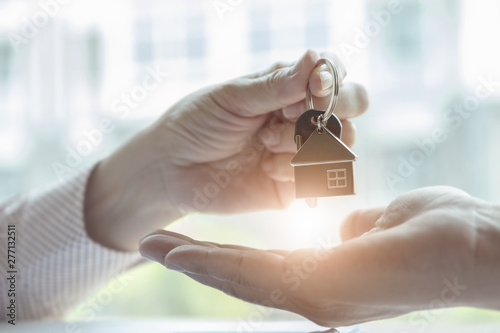 Valokuva Real estate agents agree to buy a home and give keys to clients at their agency's offices