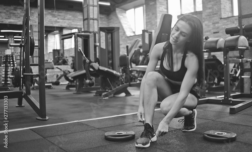 Fotografía  Attractive brunette woman tying shoelace sneakers in the gym.