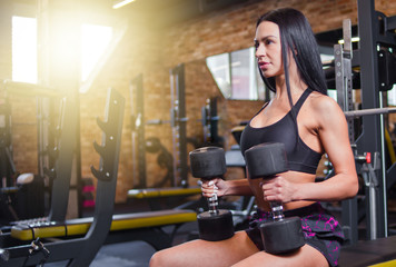 Young brunette woman in sportswear with dumbbells in her hands sitting on bench in the gym.