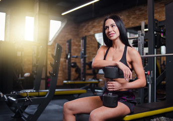 Attractive young brunette woman in sportswear with a dumbbell in her hand sitting on a bench in the gym.