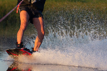 Men's Feet On A Wakeboard In Water.guy On The River And Is Preparing To Go Wake Boarding