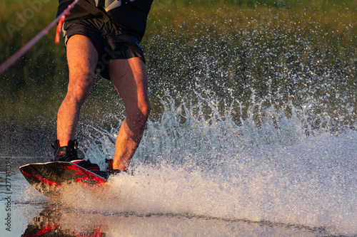 Obraz Men's feet on a wakeboard in water.guy on the river and is preparing to go wake boarding - fototapety do salonu