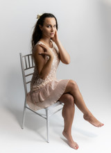 Horizontal Portrait Full Length Sitting On A White Chair On A White Background Beautiful Pretty Woman In A Fashionable Light Pink Dress, In Various Poses. Stylish Trendy Youth.