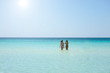Back view of two beautiful friendly women bathing in the clear sea against a sunny sky.Vacation concept.