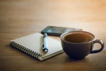 Closeup Of Notebook And Pen With Soft Focus On Black Coffee And Smartphone. Concept Rest After Work