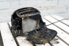 Burning Toaster. Toaster With Two Slices Of Toast Caught On Fire Over White Background
