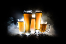 Creative Concept. Beer Glasses On Wooden Table At Dark Toned Foggy Background.