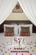 Luxury hotel bedroom interior with honeymoon decoration, Towel swans and rose flowers on the bed