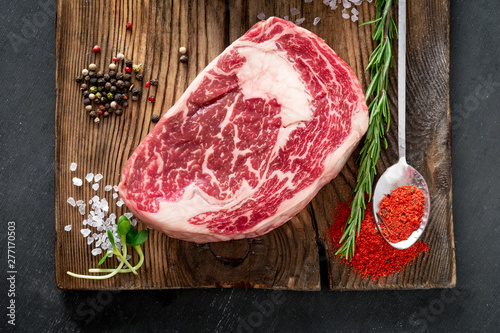 Poster de jardin Steakhouse Fresh raw rib eye steak of marble beef seasoned with pepper and salt on a wooden Board for grilling