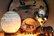 canvas print picture - Souvenirs from South Africa - plates with animals, an ostrich egg and an elephant stone figure on a dark illuminated background