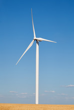 Wind Turbine In The Field Against Blue Sky With Slight Moving