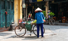The Street Vendor With Bike Loaded Of Tropical Fruits In Old Town Street In Hanoi, Old Houses And Street Activites On Background