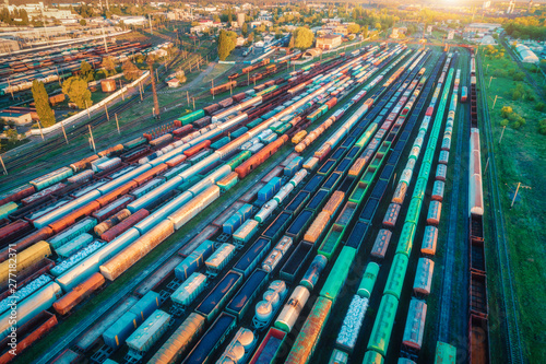 Spoed Foto op Canvas Spoorlijn Aerial view of freight trains. Colorful cargo wagons on railway station. Wagons with goods on railroad. Heavy industry. Industrial landscape with train, railway platfform at sunset. Top view. Depot