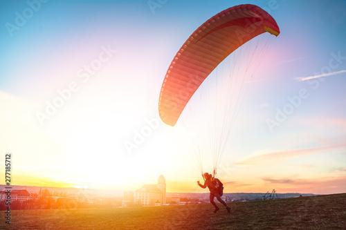 plakat Paraglider getoff ground with wind against sunset