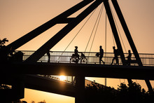 Düsseldorf 2019: Silhouette Of Several Pedestrians And A Female Person Riding A Bike On The Bridge Over The Rhine In Sunset