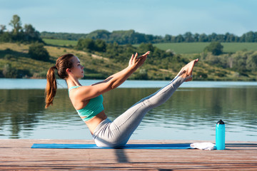 Sporty young woman doing stretching while sitting in Paripurna Navasana exercise, balance posture. Beautiful athletic girl practicing yoga against the backdrop of beautiful nature..