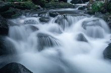 Blurred Motion Of Water Flowing Through River Rocks.
