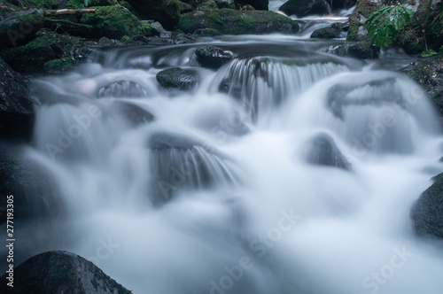 Aluminium Prints Forest river Blurred motion of water flowing through river rocks.