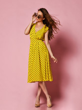 Beautiful Girl In A Romantic Dress Smiling Pretty On A Purple Background. Slender Curly Female Model In A Yellow Polka Dot Dress