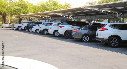 Closeup of rear, back side of white car with  other cars parking in parking lot under roof in bright sunny day.  - 277198157