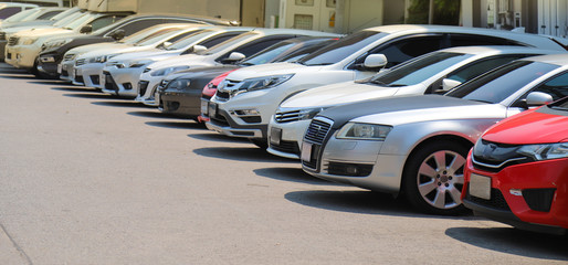 Closeup of front side of cars parking in outdoor parking lot beside the street in bright sunny day.