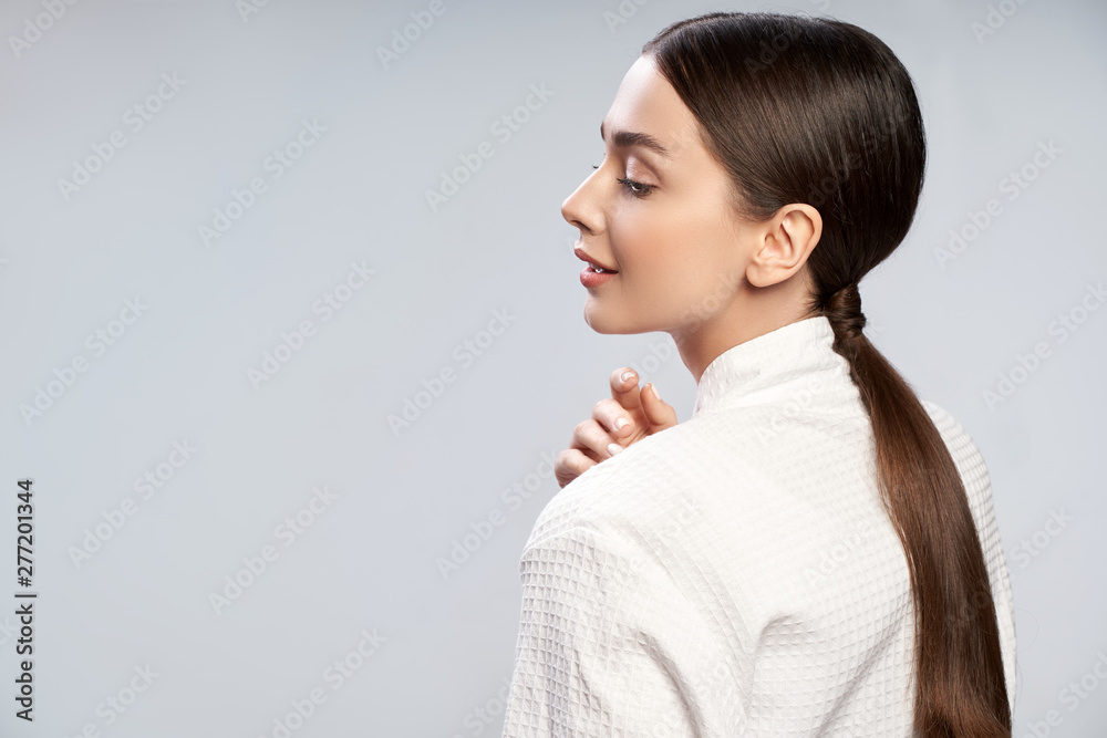 Fototapety, obrazy: Charming young woman with ponytail standing against light blue background