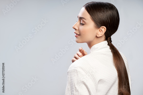 Fototapeta  Charming young woman with ponytail standing against light blue background