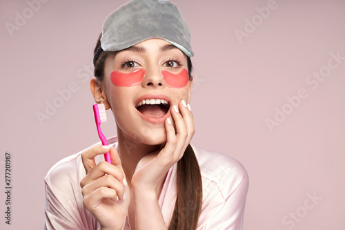 Fototapeta Charming girl with under-eyes patches holding toothbrush and touching her face