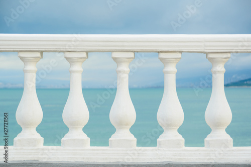 Photo classic white balustrade with stone columns on blue sky and black sea water back