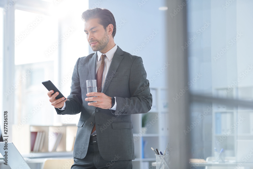 Fototapety, obrazy: Young confident agent with glass of water scrolling in smartphone