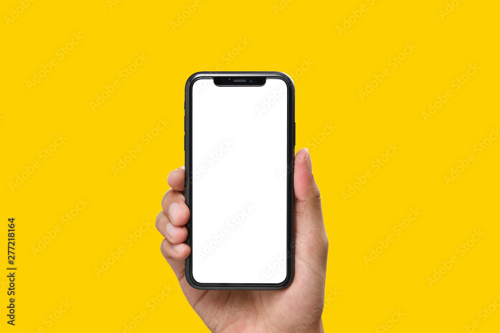Fototapety, obrazy: Hand holding the black smartphone with blank screen and modern frame less design on yellow colour background