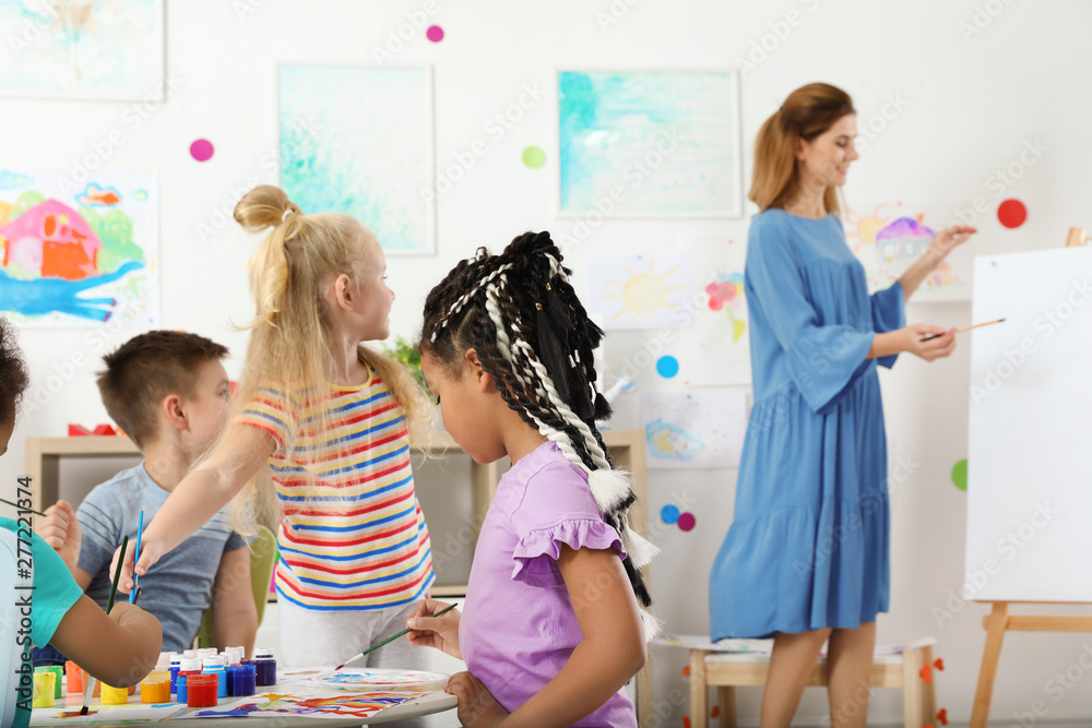 Fototapety, obrazy: Children with female teacher at painting lesson indoors