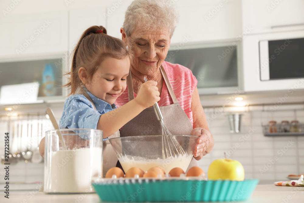 Fototapety, obrazy: Cute girl and her grandmother cooking in kitchen