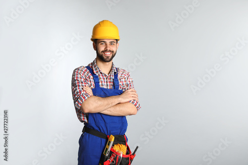 Stampa su Tela  Portrait of construction worker with tool belt on light background