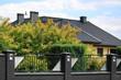 Murowane ogrodzenie z cegły i stali, dach budynku i zielone drzewa.