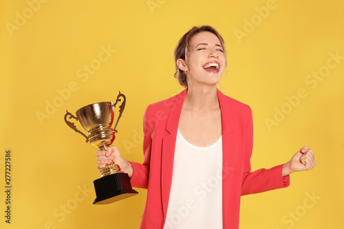 Pinturas sobre lienzo  Portrait of happy young businesswoman with gold trophy cup on yellow background