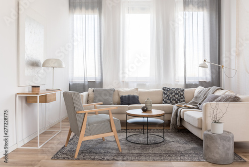 Fotografie, Obraz  Round wooden coffee table in front of scandinavian corner sofa with pillows
